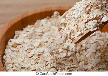 oat flakes drop from wooden spoon