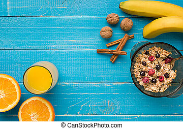 oatmeal porridge with banana, kiwi fruit, nuts and honey in a bowl with egg for healthy breakfast on rustic wooden background. top view