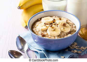 Oatmeal porridge with banana, walnuts and honey in bowl on purple wooden background. Healthy breakfast.