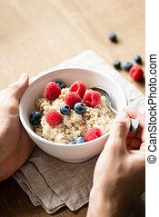 Oatmeal porridge with berries in hands