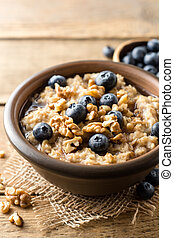 Oatmeal porridge with blueberries, walnuts and honey in ceramic bowl on wooden background.