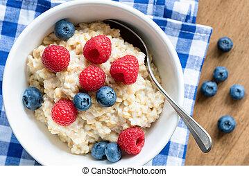 Oatmeal porridge with fresh berries, closeup view