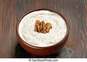 Oatmeal porridge with walnuts on wooden table, close up view