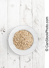Oatmeal. Rolled oats flakes on white wooden background