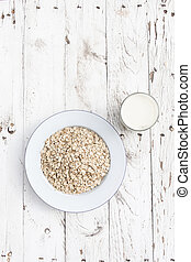 Oatmeal, rolled oats on a plate with glass of milk on white wooden table. Porridge oats, used in granola or muesli. Copyspace, flat lay