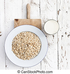 Oatmeal, rolled oats on white wooden background wilt glass of milk. Porridge oats, used in granola or muesli. Large whole flakes. Copyspace, flat lay