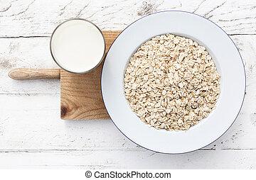 Oatmeal, rolled oats on white wooden background wilt glass of milk. Porridge oats, used in granola or muesli. Breakfast concept
