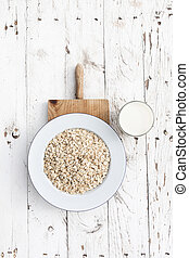 Oatmeal, rolled oats on white wooden background wilt glass of milk. Porridge oats, used in granola or muesli.