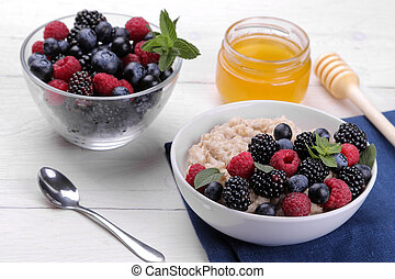 Oatmeal with berries and honey in a bowl on a white wooden table. breakfast. healthy food.
