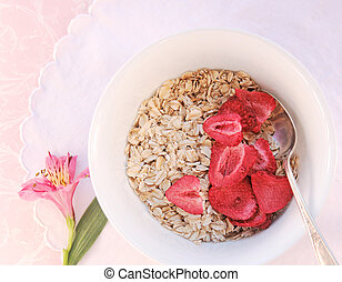Oatmeal with dried strawberries - Bowl of raw oatmeal and...