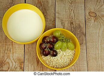 Oatmeal with grapes and milk on a wooden countertop