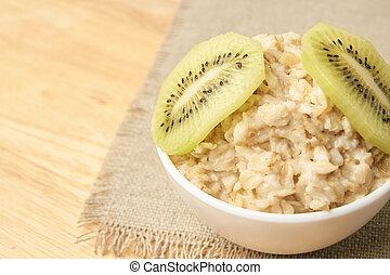 Oatmeal with kiwi. Useful breakfast. Neutral background