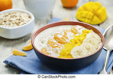 Oatmeal with mango, banana, tangerine oranges and coconut flakes