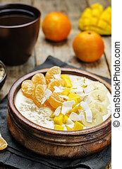 Oatmeal with mango, banana, tangerine oranges and coconut flakes