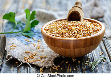 Oats and wooden scoop in a bowl.