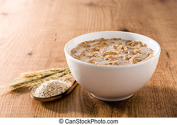 Oats milk and cereals on wooden table.