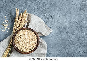 Oats, oat flakes, rolled oats in wooden bowl