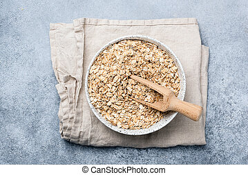 Oats or oat flakes in bowl on linen textile