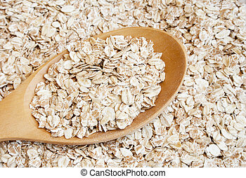 Oats seed in spoon - Dry rolled oats seed in wooden spoon