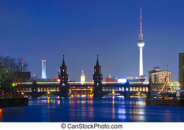 oberbaum bridge and tv tower in berlin, germany, at night