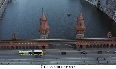 Oberbaum Bridge in Berlin, Germany and Yellow Bus passing over Spree River in Daylight, Aerial Tilt Down Dolly forward wide shot 4K