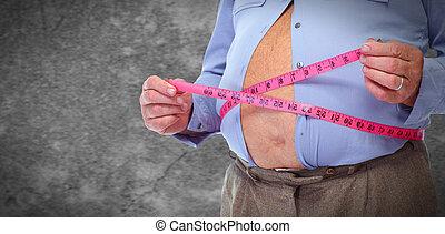Obese man abdomen with measuring tape.