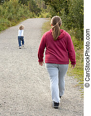 Obese mother and child walking on a forest path