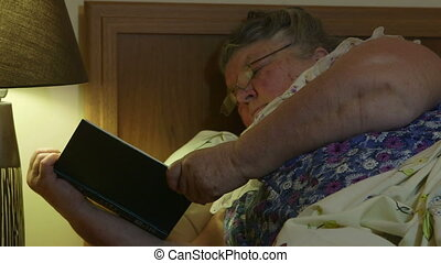 Obese old lady lying in bed at home reading book close-up