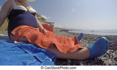 Obese senior woman in swimwear relaxing on the beach low-angle view