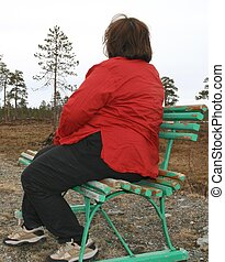 Depressed obese woman sitting on a bench