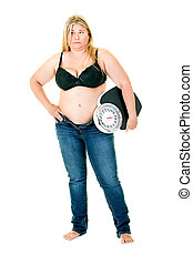 Obese young woman in bra and jeans with weighing scales under arm
