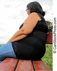 Obese middle aged woman sitting on a bench