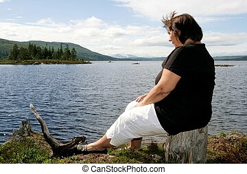 Obese woman sitting by a lake