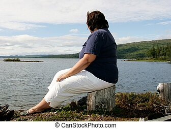 Obese woman sitting by a lake in a mountain area