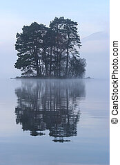 obscure scot island - Small tree-covered island rises out of...