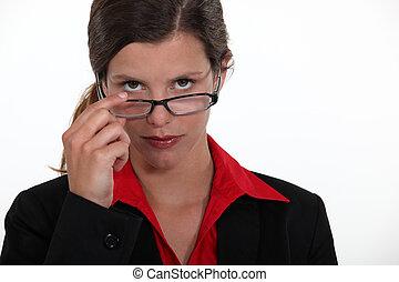 Observant woman peering over her glasses