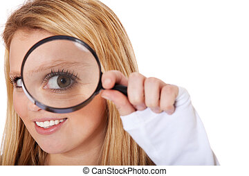 Attractive teenage girl looking through magnifier. All on white background.