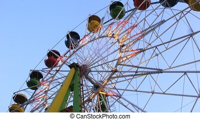 Observation wheel works in evening in park closeup, time...
