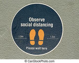 Observe social distancing sign