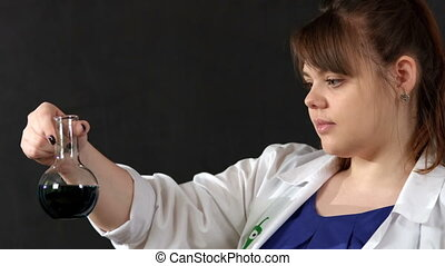 Observing a chemical reaction - Female scientist examines a...