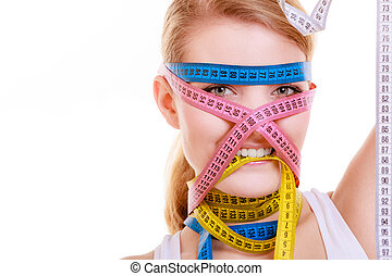 Obsessed sporty fit woman with measure tapes. Time for diet slimming.