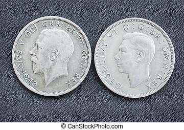 Obverse side of two half crown British coins, one of king George V (from 1920) , the other his son George VI (from 1946).