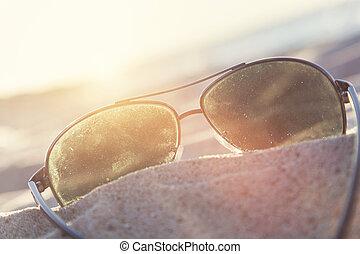 occhiali da sole, su, sabbia, a, tramonto, spiaggia, e, oceano, in, il, fondo.