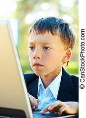 Occupation - Portrait of smart boy working with laptop with ...