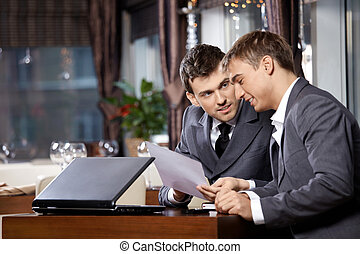 Two businessmen at restaurant discuss the document