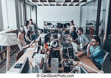occupato, giorno feriale, in, ufficio., gruppo, di, giovane, persone affari, in, casuale astuto, indossare, lavorativo, e, comunicare, mentre, seduta, a, il, grande, scrivania, in, ufficio, insieme
