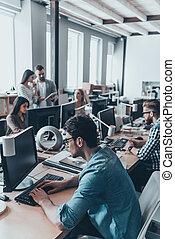 occupato, lavorativo, day., gruppo, di, giovane, persone affari, in, casuale astuto, indossare, lavorativo, e, comunicare, mentre, seduta, a, il, grande, scrivania, in, ufficio, insieme