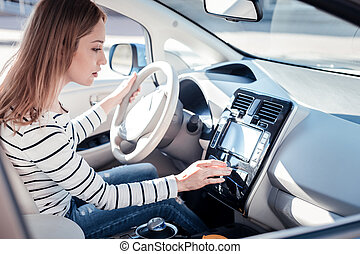 Occupied interested woman sitting in the car holding touching control panel.