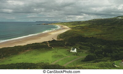 Ocean bay sandy beach aerial panoramic view under gray thick clouds. Green grass meadows valleys with white houses. People walking and looking at wonderful scenery of Irish nature. Shooting in 4K, UHD