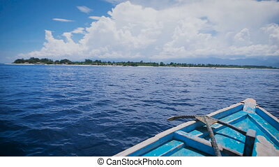 Ocean island of Bali. Boat tour. Young man in a boat on the ocean excursions. Stunningly clear ocean, year-round sunshine, paradise island - idyllic picture.